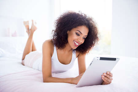Portrait of positive charming youth student lie bed feel cheerful excited enjoy satisfied content use user modern technology chatting blogger blog wavy curly haircut brunette nightwear apartment