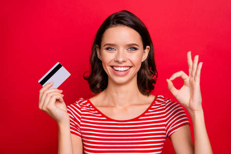 Close up photo cheerful charming lady positive satisfied advert alright good like fine choice decision advice promoter news discount black friday striped t-shirt trendy stylish isolated red background Stock fotó - 123916562