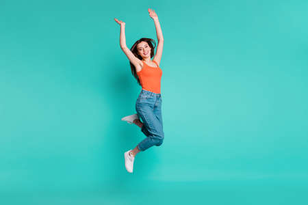 Full length side profile body size photo beautiful her she lady jump high amazed excited easy-going weekend vacation wear casual orange tank-top jeans denim isolated bright teal turquoise background