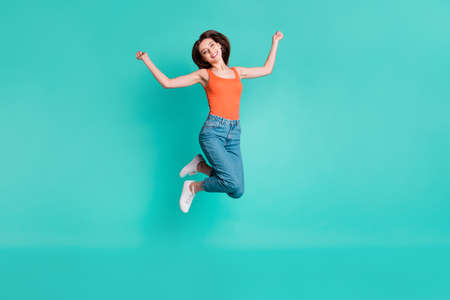 Full length side profile body size photo beautiful her she lady jump high excited easy-going weekend vacation wear casual orange tank-top jeans denim isolated bright teal turquoise background