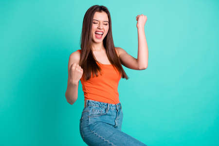 Close up side profile photo beautiful yelling yeah her she lady arms hands fists raised champion football competition wear casual orange tank-top jeans denim isolated bright teal turquoise background