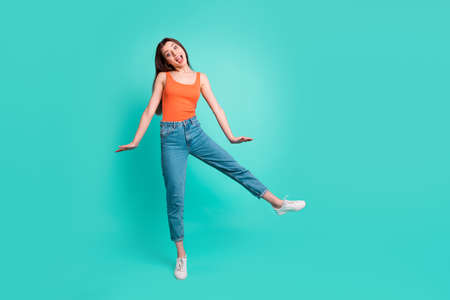 Full length body size photo beautiful her she lady easy-going person weekend vacation mood freedom active energy wear casual orange tank-top jeans denim isolated bright teal turquoise background