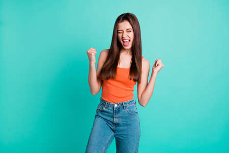 Close up photo beautiful yelling yeah her she lady hold arms hands fists raised air champion football competition wear casual orange tank-top jeans denim isolated bright teal turquoise background