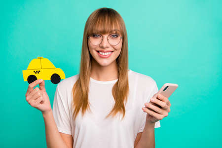 Close up photo beautiful she her lady arm hold telephone smart phone paper yellow taxi car advising use user best speed fast service wear specs casual white t-shirt isolated teal green background