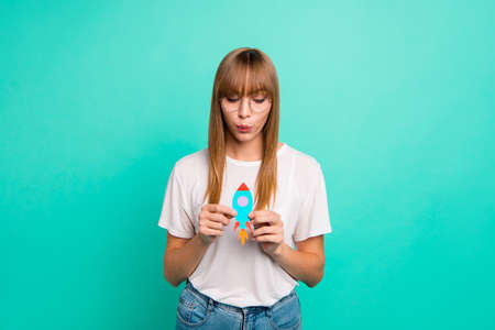 Close up photo amazing beautiful she her lady arm hand paper rocket show imaginary inspiration flight open cosmic space galaxy wear specs casual white t-shirt isolated teal green background