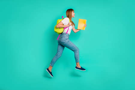 Full length side profile body size photo beautiful she her lady jump high arms hands hold back pack notebooks on way school friendly wear specs casual white t-shirt isolated teal green background