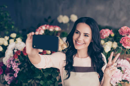 Close-up portrait of her she nice attractive lovely charming cute gorgeous winsome cheerful mature wavy-haired lady salon decor director taking selfie showing v-sign positive workplace Stock fotó