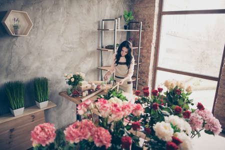 Nice charming attractive gorgeous focused concentrated wavy-haired lady making perfect desirable fresh birthday celebratory pleasant decorative gift industrial loft interior concrete wall workplace