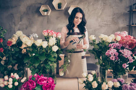 Portrait of her she nice gorgeous attractive charming cute wavy-haired lady garden care seller specialist employee employment cutting stem hydrangeas order client concrete wall indoors workstation. Фото со стока