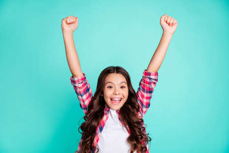 Portrait of cute nice trendy stylish kid astonished impressed aims contest lottery fortune scream omg wow unbelievable unexpected raise fists shout wear checked modern outfit isolated teal background.
