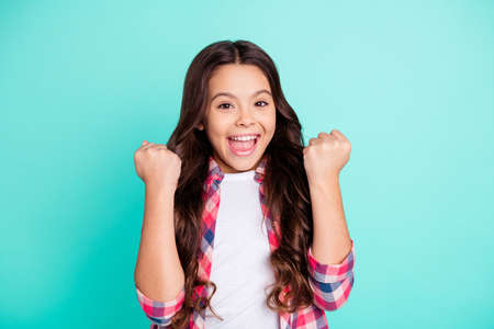Portrait of cute charming nice girl children raise fists scream get aim gamer lucky fortune goal fan wear plaid fashionable clothes isolated green background. Фото со стока