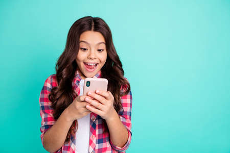 Portrait of her she nice attractive lovely charming cute cheerful cheery wavy-haired pre-teen girl in checked shirt browsing online isolated over bright vivid shine green blue turquoise background Reklamní fotografie