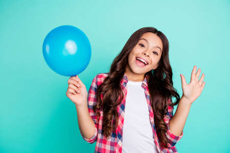 Portrait of her she nice cute attractive cheerful wavy-haired girl in checked shirt holding in hand ball festive celebratory having fun isolated on bright vivid shine green blue turquoise background