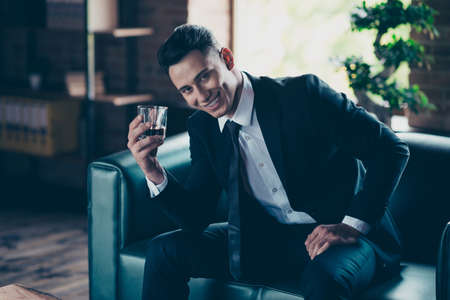 Close up photo handsome he him his perfect white teeth hands arms whisky beverage enjoy pause break toasting wear formal-wear dress code shirt jacket tie suit costume sit chair indoors office place Stockfoto