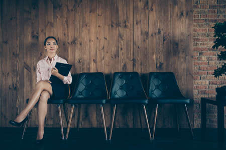 Portrait of nice attractive elegant confident content lady qualified specialist sitting on chair waiting appointment meeting recruiter at modern industrial loft interior style work place station