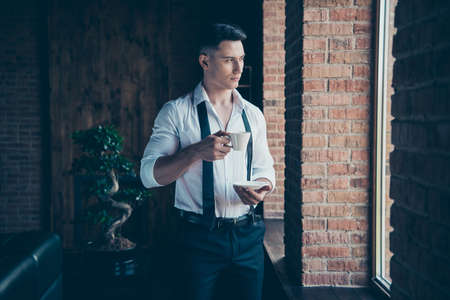 Close up photo handsome amazing he him his wondered hands arms hold hot beverage look window dream dreamy imaginary flight wear formal-wear dress code shirt stand indoors modern office place