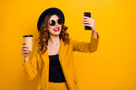 Close up photo beautiful funky she her lady hands arms telephone make take selfies tongue out mouth vacation hot beverage paper container wear specs formal-wear suit isolated yellow bright background