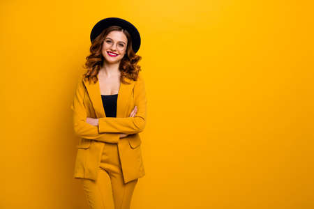 Portrait d'elle, elle, jolie, charmante, mignonne, séduisante, séduisante, charmante, élégante, élégante, gaie, aux cheveux ondulés, en veste jaune, blazer, bras croisés, isolée sur fond orange brillant et brillant