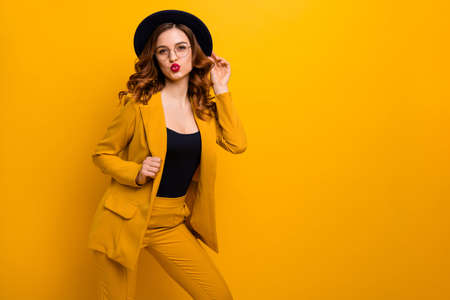 Portrait of her she nice charming cute attractive lovely winsome sweet fashionable chic cheerful wavy-haired lady wearing yellow jacket sending kiss isolated on bright vivid shine orange background