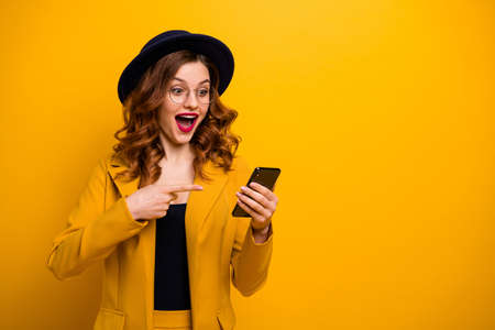 Close up photo beautiful yell she her lady direct indicate arm hand telephone reader cool news modern look sale discount lottery wear specs formal-wear costume suit isolated yellow vibrant background