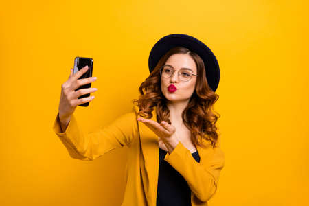 Close up photo beautiful funky she her lady arm hand arm telephone make take selfies send air kisses boyfriend leisure rejoice wear specs formal-wear costume suit isolated yellow vibrant background