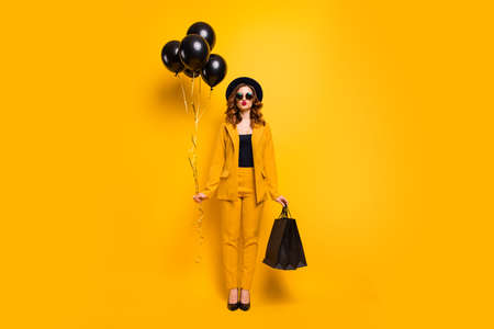 Full length body size photo beautiful she her lady send air kiss carry packs perfect look festive guest birthday presents balloons wear specs formal-wear costume suit isolated yellow bright background