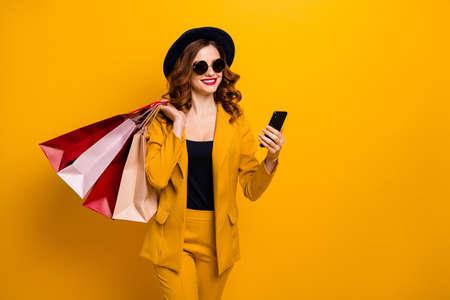 Cerrar foto hermosa ella su dama manos brazos teléfono muchos paquetes comprador vacaciones viajero venta descuento buscar gps siguiente boutique desgaste especificaciones traje formal aislado amarillo brillante fondo