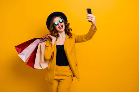 Close up photo beautiful she her model lady hands arms telephone many packs buyer vacation traveler sale discount skype blog translation wear specs formal-wear suit isolated yellow bright background Stock fotó