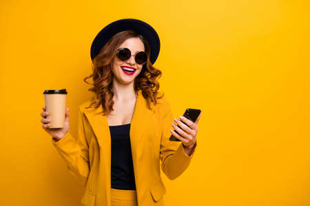 Close up photo beautiful funky she her lady hands arms telephone vacation traveler hot beverage paper container laugh laughter reader wear specs formal-wear suit isolated yellow bright background