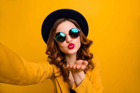 Close up photo beautiful dreamy funky she her lady make take selfies send air kiss boyfriend vacation red pomade lips lipstick wear hat sun specs formal-wear suit isolated yellow bright background Banque d'images - 124259499