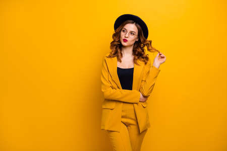 Portrait of her she nice charming cute attractive lovely winsome sweet gorgeous chic cheerful wavy-haired lady wearing yellow jacket playing with curls isolated on bright vivid shine orange background