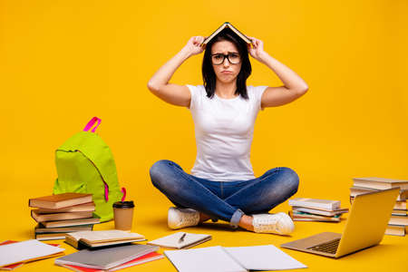 Full length body size photo beautiful she her sit floor hands arms take book head messy urgency homework overworked need rest wear casual white t-shirt jeans denim isolated bright yellow background