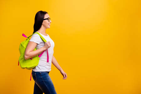 Close up side profile photo beautiful she her lady backpack going meet classmates groupmates before classes lessons wear specs casual white t-shirt jeans denim isolated bright yellow background