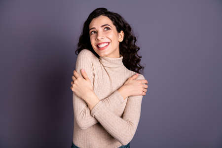 Close up photo beautiful she her lady look up empty space copyspace overjoyed toothy beaming smile hold hands arms shoulders nice clothes wear casual pastel sweater pullover isolated grey background Stock Photo