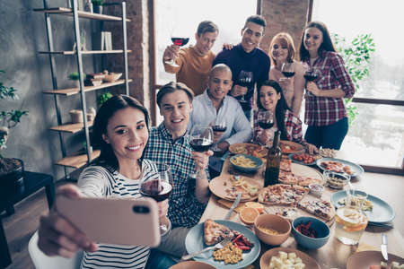 Close up photo friendly event together diversity different race guys raise glasses red beverage telephone make take tradition selfies sit table shirts sweater pullover loft cafe restaurant indoors