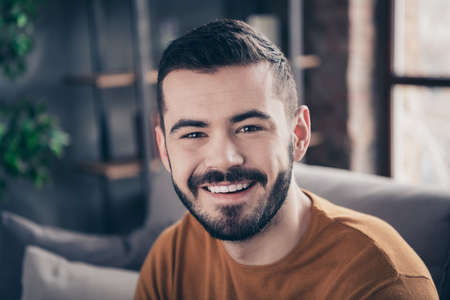 Close-up portrait of his he nice-looking attractive bearded cheery cheerful confident content guy spending spare time at industrial loft interior style living-room indoors