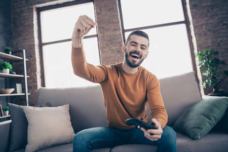 Portrait of his he nice-looking attractive bearded cheerful cheery glad guy spending weekend sitting on divan winning xbox entertainment at industrial loft brick interior style living-room indoors