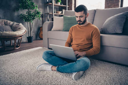 Portrait of concentrated focused man youth sit lotus position look read data statistics management denim jeans orange pullover sweater big light interior