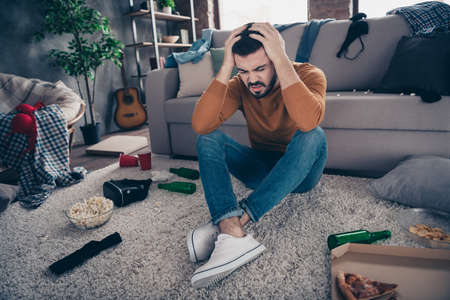 Close up photo of disappointed man student touch head hands hand match celebrate close eyes messy denim jeans orange pullover sweater big light apartment room