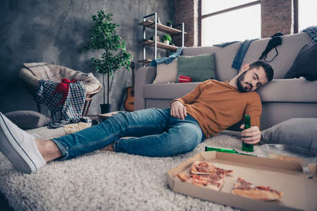 Portrait of sleepy funny funky post-graduate student lying had feast festival birthday anniversary close eyes denim jeans orange pullover sweater hold hand big light apartment Stock Photo