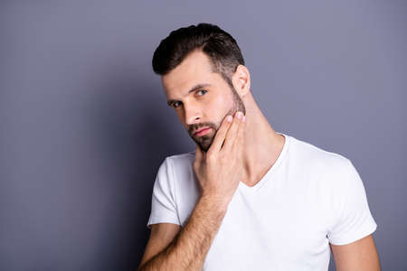 Close up photo amazing he him his macho perfect appearance touch arm hand neat bristle face calm not smiling ponder pensive look mirror bath shower wear casual white t-shirt isolated grey background