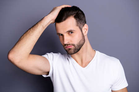 Close up photo amazing he him his macho perfect appearance touch arm hand groomed head haircut stylist visit not smiling calm look mirror shower wear casual white t-shirt isolated grey background