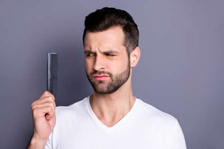 Close up photo amazing he him his macho deny not sure action new hand arm plastic hair styling brush take care hairdo after barber shop stylist visit wear casual white t-shirt isolated grey background