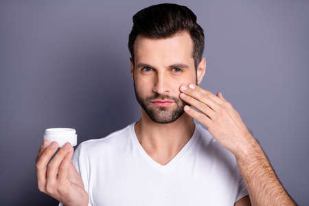 Close up photo amazing he him his macho perfect ideal appearance neat stubble advising recommending buy buyer hold hand arm novelty facial cream wear casual white t-shirt isolated grey background