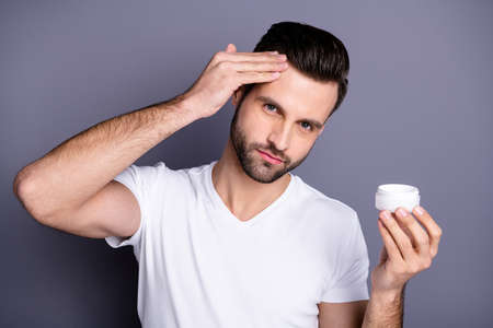 Close up photo amazing he him his macho perfect ideal appearance neat stubble advising buy buyer hold hand arm novelty smearing temple facial cream wear casual white t-shirt isolated grey background Stock Photo