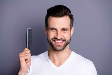 Close up photo amazing he him his macho advising buy buyer new hand arm plastic hair styling brush take care hairdo after barber shop stylist visit wear casual white t-shirt isolated grey background