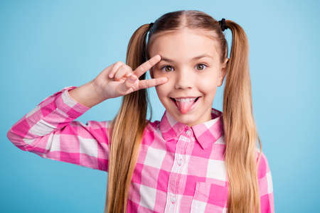 Close up photo beautiful amazing she her little lady hand v-sign symbol near eye tongue out mouth giggle playful vacation mood wear casual checkered plaid pink shirt isolated bright blue background