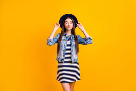 Portrait of her she nice-looking sweet attractive lovely lovable fascinating tender straight-haired lady touching hat closed eyes isolated over bright vivid shine yellow background