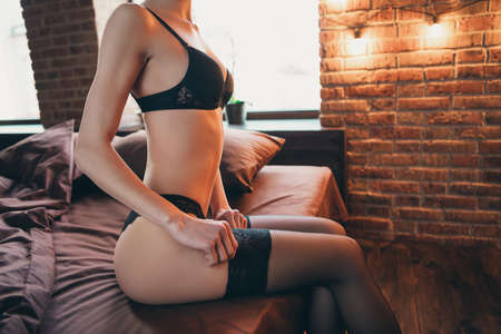 Cropped close up side profile photo beautiful half-naked she her lady hands arms, dressing put on lace tights tempting flirty coquette slim waist legs ass stockings bikini boudoir room indoors