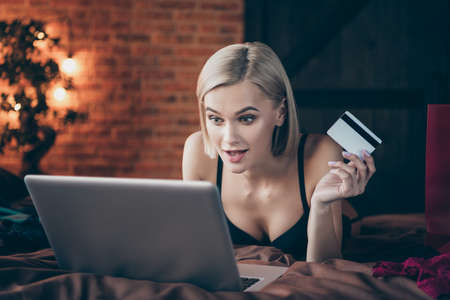 Close-up portrait of her she nice-looking gorgeous chic attractive lovely cheerful glad lady lying on bed buying goods on web site wireless order in loft brick industrial style interior house indoors Banco de Imagens